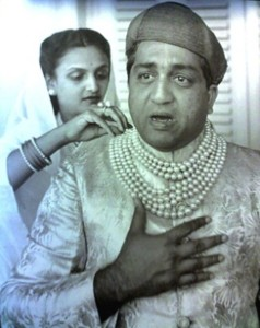 Maharajah Pratapsingh Rao Gaekwad wearing the Baroda pearl necklace in its original state. His wife, Sita Devi, is in the background.